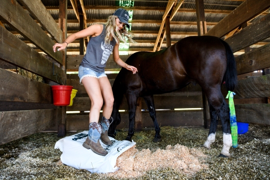 St. Paul Rodeo Queen Melanie Atchison jumps on a bag of shavings as she cleans her horse Shady's stable on Friday, June 30, 2017.